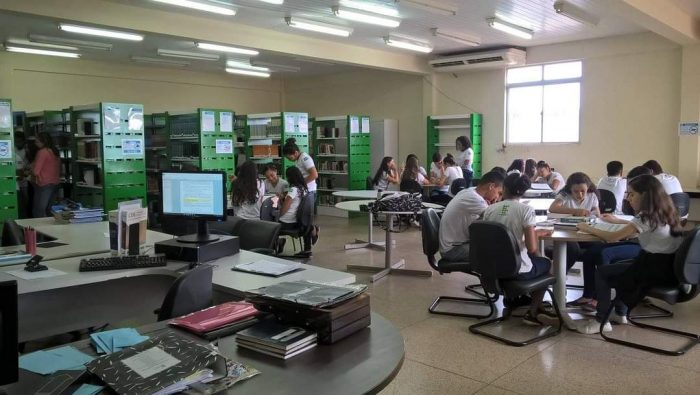 Biblioteca Machado de Assis do Campus Zé Doca. Com mesas redondas e alunos ao redor delas cadeiras com alunos estudando. Ao fundo estantes de livros.